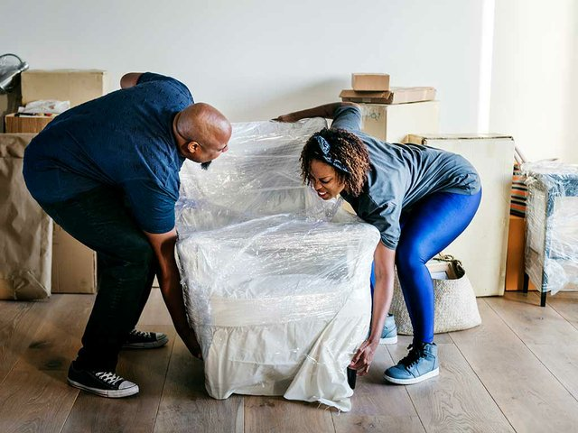 couple-moving-wrapped-chair.jpg