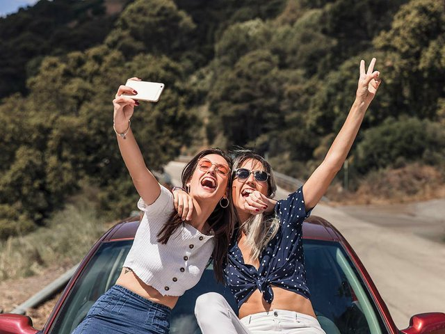 female-friends-sitting-car-hood-taking-self-portrait.jpg