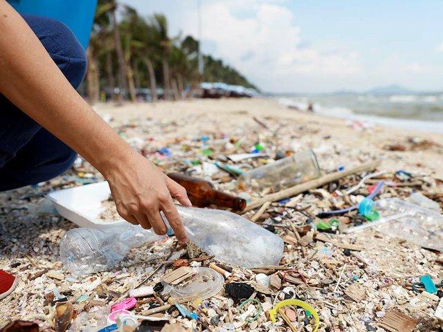 volunteer-tourist-hand-clean-up-garbage-plastic-debris-dirty-beach-into-big-blue-bag.jpg