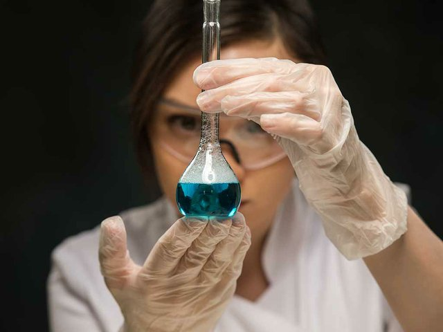 female-scientific-researcher-holding-glass-test-tube.jpg