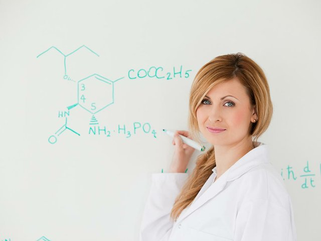 female-scientist-looking-camera-while-writing-formula-white-board.jpg