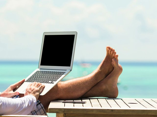 young-man-with-tablet-computer-during-tropical-beach-vacation.jpg