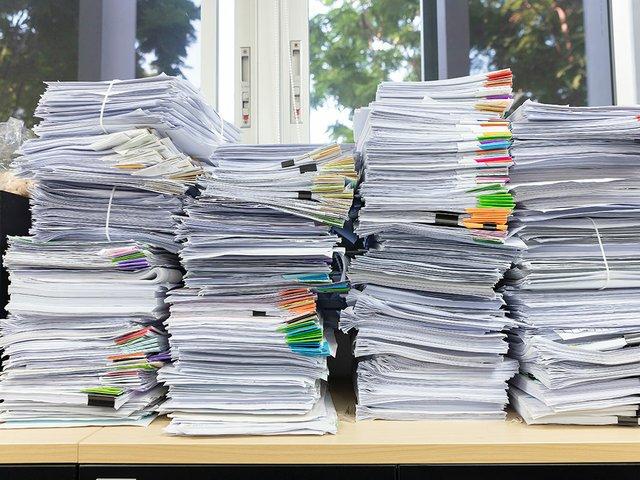 pile-unfinished-documents-office-desk.jpg
