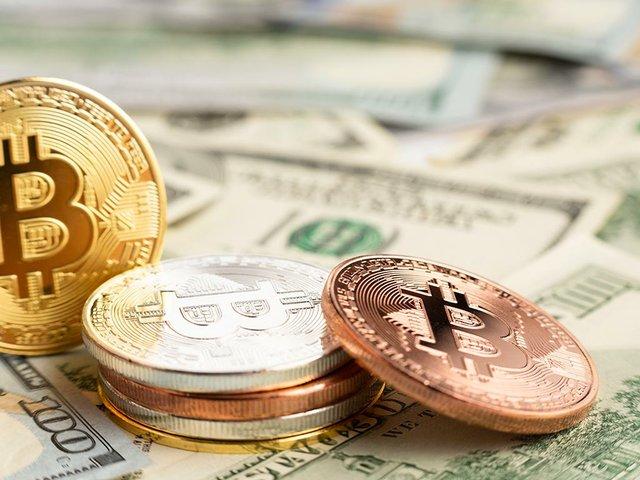 bitcoin-pile-top-dolar-bills.jpg