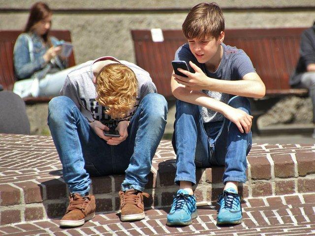2-boy-sitting-on-brown-floor-while-using-their-smartphone-159395.jpg