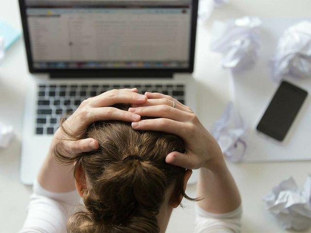 portrait-woman-grabbing-head-desk-near-laptop.jpg