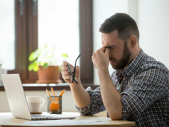 stressed-male-massaging-nose-bridge-suffering-from-headache.jpg