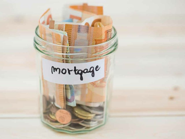 folded-euro-notes-coins-mortgage-glass-jar-wooden-backdrop.jpg