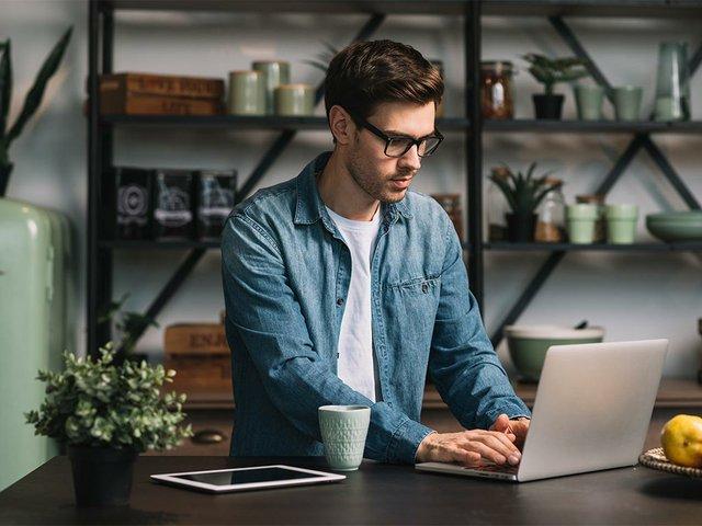 hombre-joven-anteojos-usando-laptop-cocina.jpg