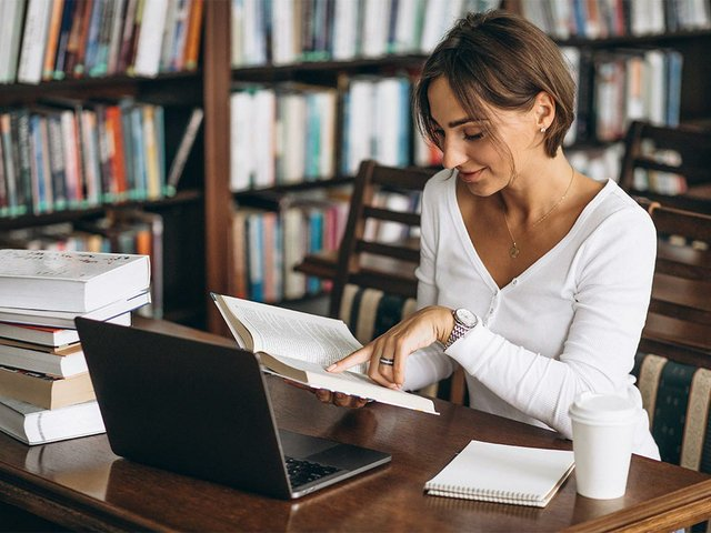 young-woman-sitting-library-using-books-computer.jpg