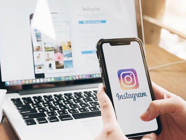 mujer-sostiene-telefono-inteligente-aplicacion-instagram-pantalla-cafe.jpg