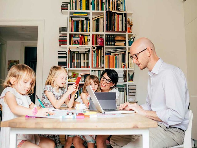 parents-indoor-sitting-table-homeschooling-with-three-female-children.jpg