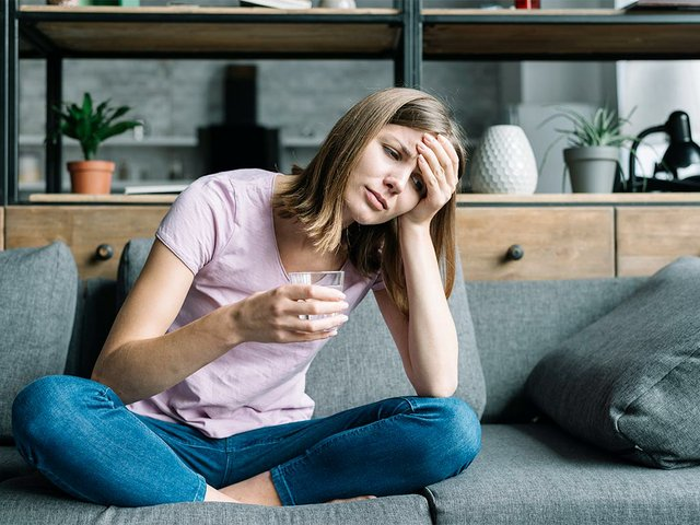 sick-young-woman-sitting-sofa-with-glass-water.jpg