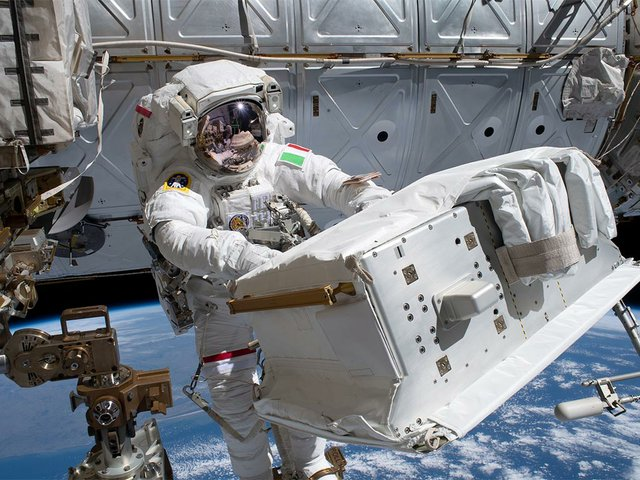 ESA-astronaut-Luca-Parmitano,-attached-to-the-Canadarm2-robotic-arm,-carries-the-new-thermal-pump-system-that-was-installed-on-the-Alpha-Magnetic-Spectrometer-ISS.jpg