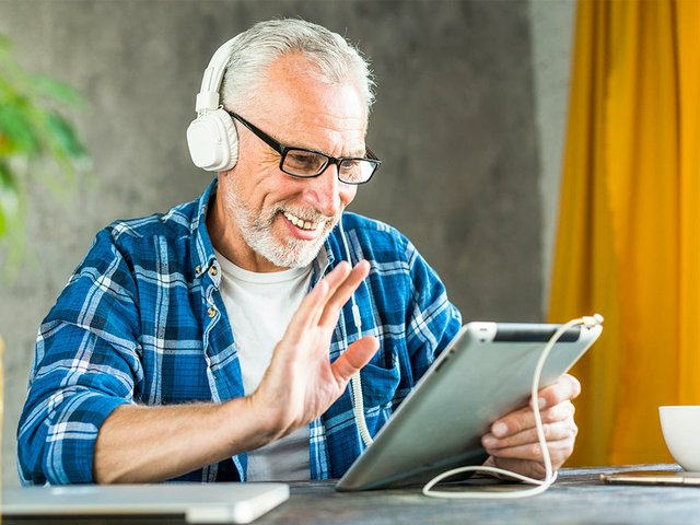 smiling-senior-man-saying-hello-digital-tablet.jpg