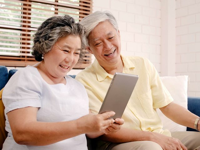 asian-elderly-couple-using-tablet-drinking-coffee-liv.jpg