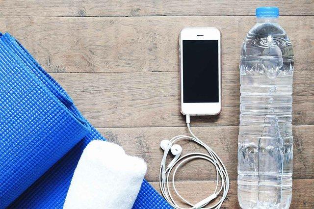 flat-lay-mobile-phone-with-earphones-water-bottle-towel-blue-yoga-.jpg