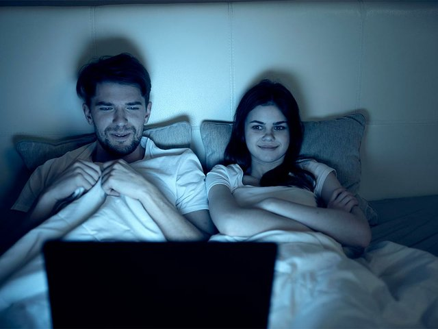 man-works-laptop-bed-beloved-woman-sleeps-night.jpg