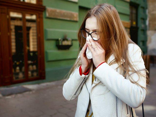 woman-sneezes-standing-street.jpg