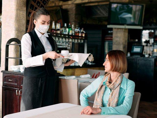 european-looking-waiter-medical-mask-serves-coffee(1).jpg