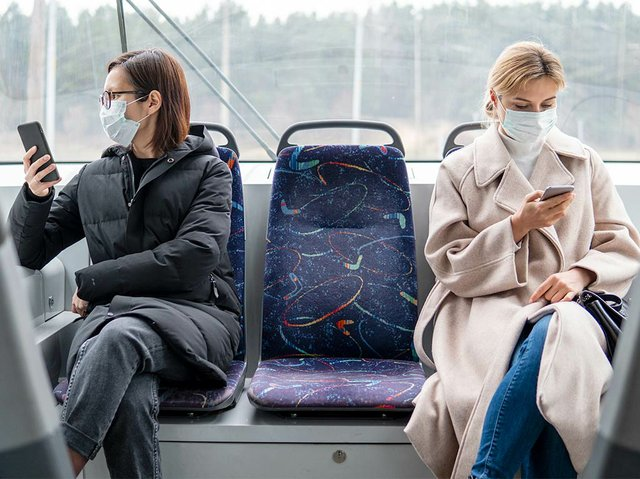 young-women-using-public-transport-with-surgical-mask.jpg