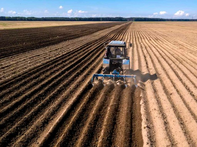 tractor-aerial-view-tractor-work-cultivating-field-spring-with-blue-.jpg