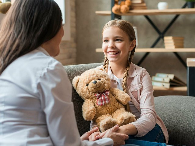 female-psychologist-talking-with-girl-holding-teddy-bear-during-therapy-session.jpg