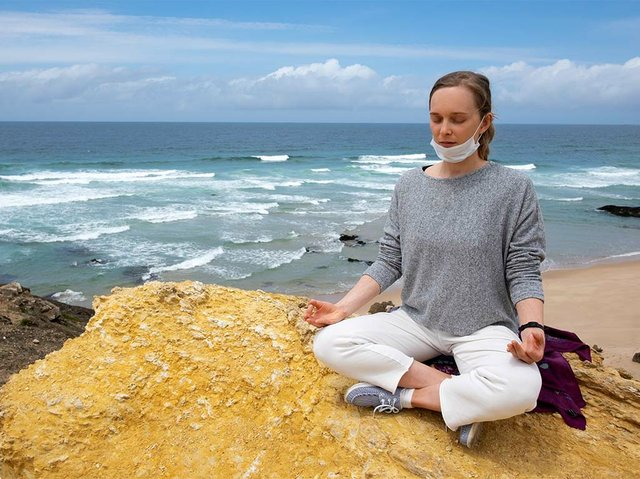 tranquil-woman-face-mask-practicing-yoga-seaside.jpg