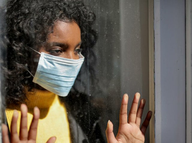 serious-young-woman-in-medical-mask-standing-at-window.jpg