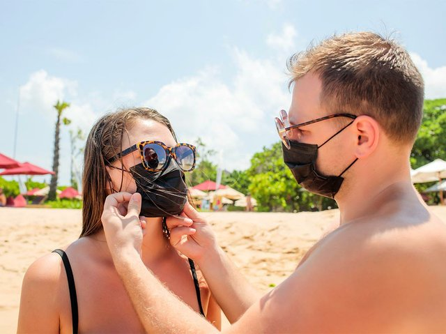 young-couple-wearing-protective-mask-beach.jpg