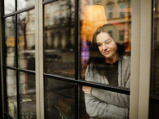 mira-exterior-encantadora-mujer-pie-pensativa-detras-ventana.jpg