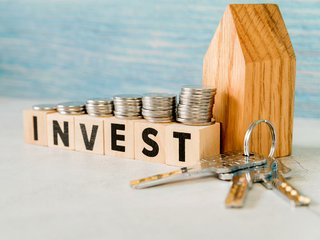 stack-coins-invest-wooden-blocks-near-house-with-silver-keys.jpg