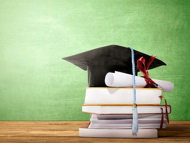 graduation-hat-diploma-scroll-books-table.jpg