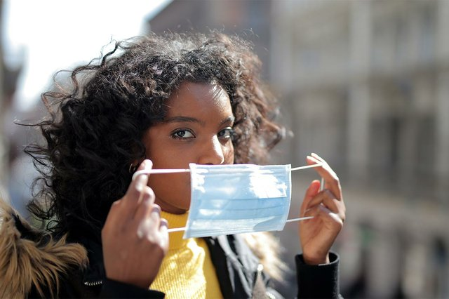 focused-young-ethnic-lady-putting-on-medical-mask-on-street.jpg