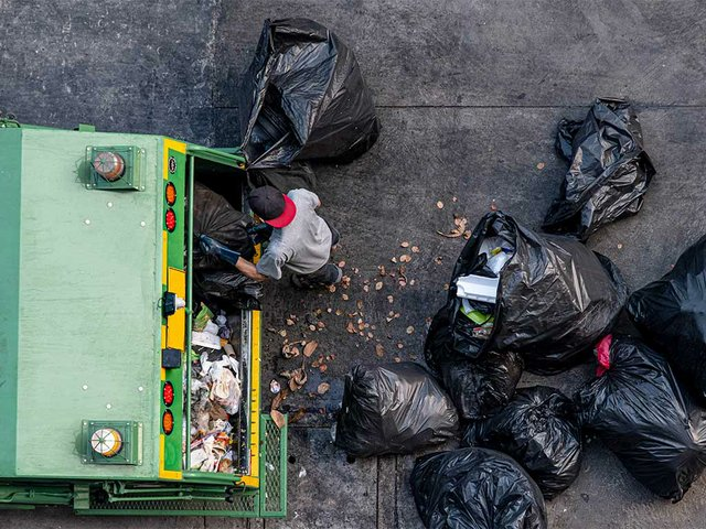 green-garbage-truck-employees-are-collecting-lot-black-garbage-bags.jpg