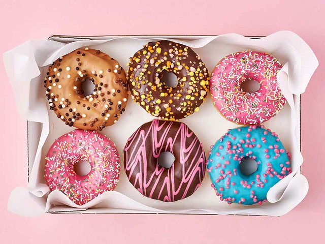 different-types-colorful-donats-decorated-sprinkles-icing-box-pink-top-view.jpg