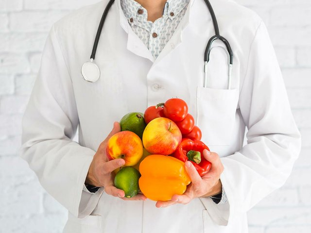 close-up-male-doctor-s-hand-holding-fresh-produce-healthy-fruit-vegetable.jpg