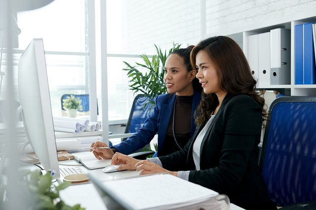 two-asian-businesswomen-sitting-together-office-desk-looking-computer.jpg