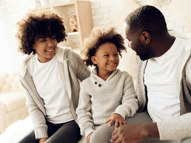 happy-family-smiling-sitting-bed-home.jpg