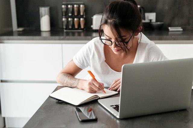 woman-using-laptop-computer-writing-in-kitchen.jpg