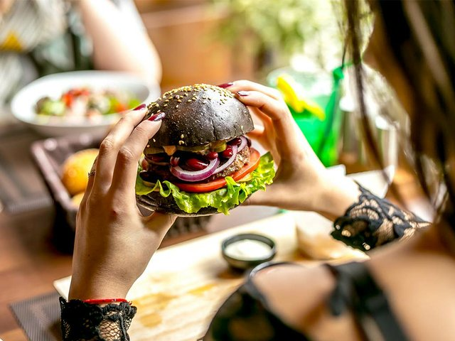 man-holding-meat-burger-tomato-onion-lettuce-side-view.jpg