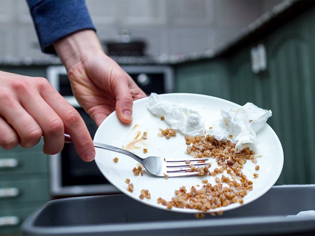 close-up-person-throwing-from-plate-leftover-buckwheat-trash-bin-scraping-food-waste.jpg