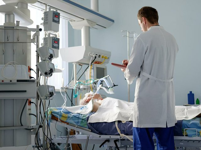 intensive-care-caucasian-doctor-examines-intubated-critical-stance-patient-writing-notes-case-report-intensive-care.jpg