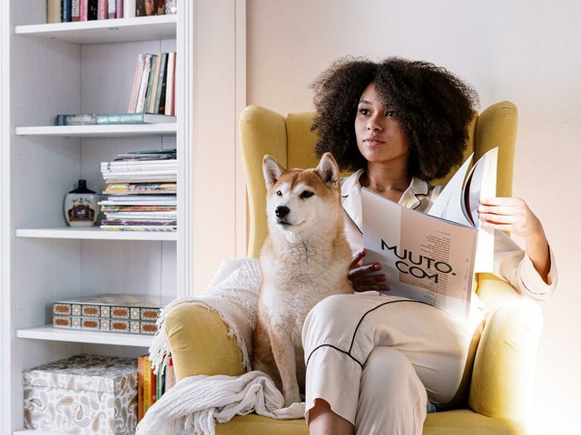 woman-sitting-in-chair-with-dog-reading.jpg