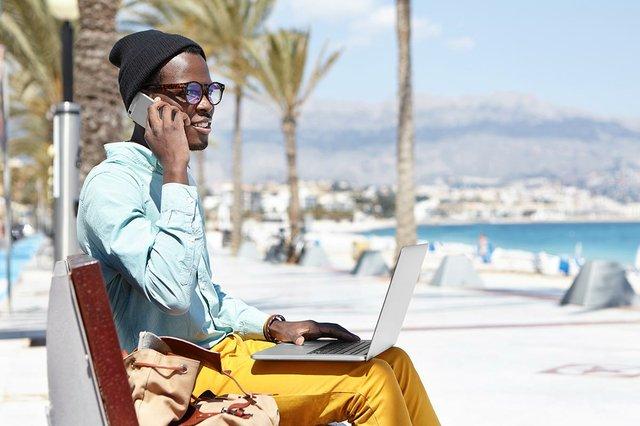 man-wearing-shades-working-beach-using-notebook-computer-talking-mobile.jpg