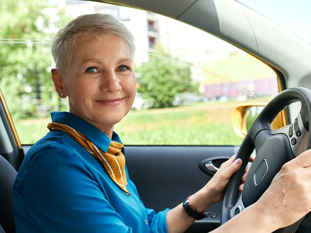 side-view-cheerful-woman-inside-car-drivers-seat-with-hands-steering-wheel.jpg
