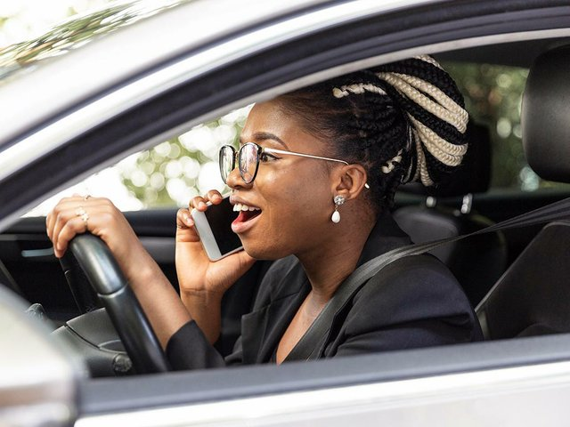 side-view-woman-talking-smartphone-while-driving-her-car.jpg