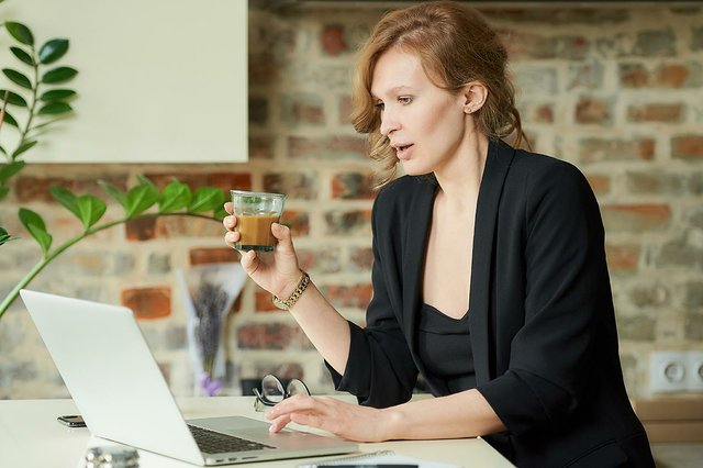woman-working-remotely-with-coffee-discussing-project-with-colleagues-video-conference-home.jpg
