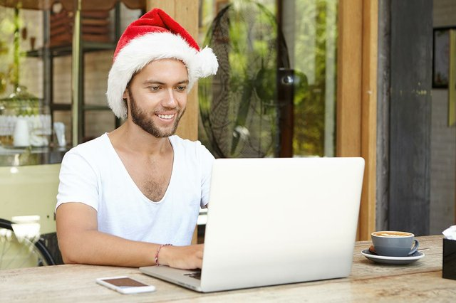 man-wearing-santa-hat-making-video-call-laptop.jpg