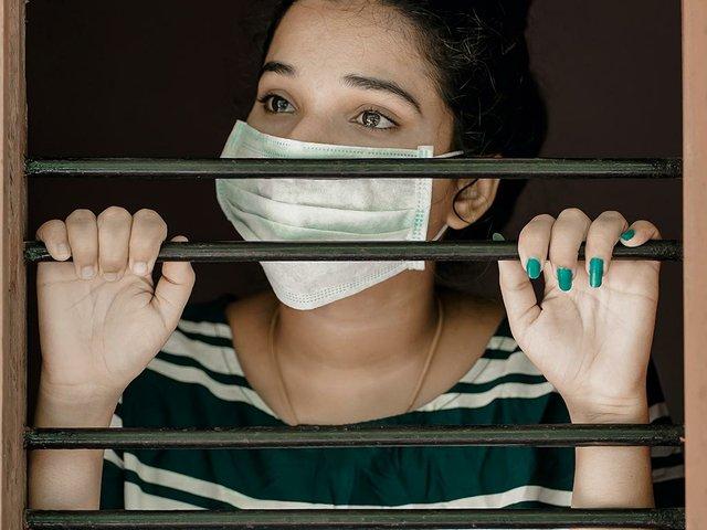 woman-with-mask-in-window.jpg